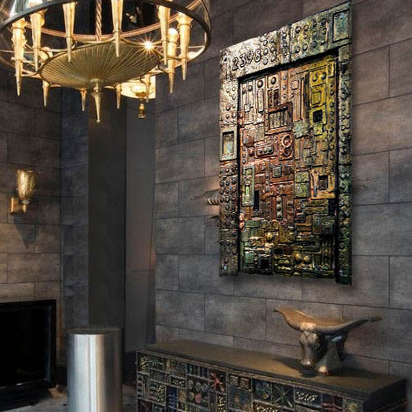 Bronze and metallic featured wall art in Gothic style entryway with gold chandelier.