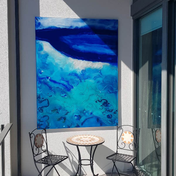 Barrier Reef themed glass wall art with wrought iron cafe table and chairs.