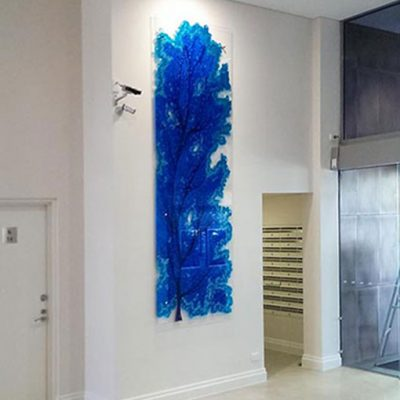 Blue fern glass wall art feature displayed in hotel foyer.