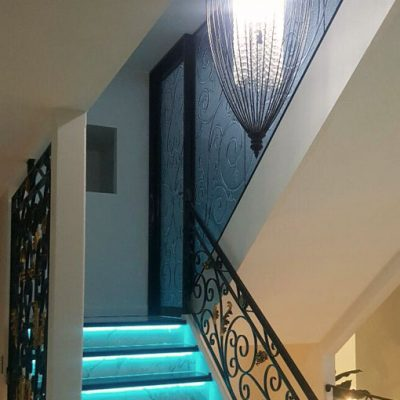 Slumped glass staircase with ornate wrought iron balustrade.